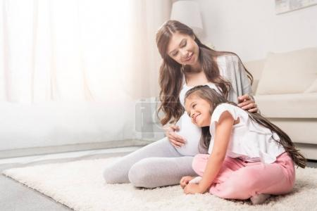 Photo for Pregnant woman with her little daughter listening to her belly. - Royalty Free Image