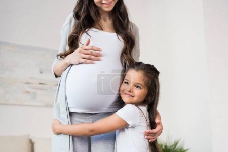 Girl hugging pregnant mother