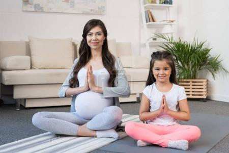 Pregnant woman with daughter in lotus pose