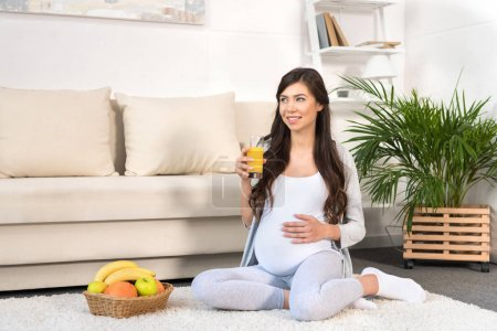 Pregnant woman holding glass of juice