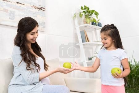 Pregnant mother giving apple to daughter