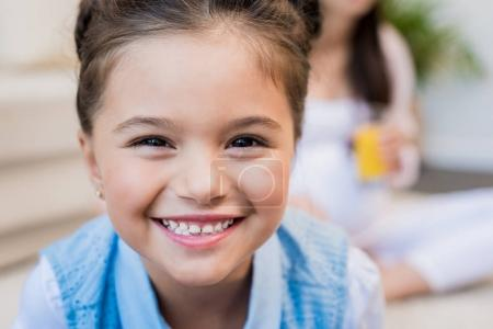 Photo for Closeup shot of a little girl smiling and looking into camera. - Royalty Free Image