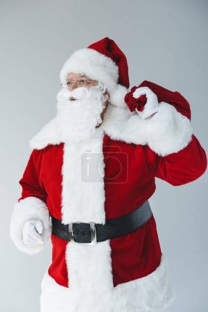 Photo for Santa claus in eyeglasses holding bag and looking away isolated on white - Royalty Free Image