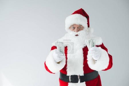 Photo for Shocked santa claus holding dollar banknotes isolated on white - Royalty Free Image