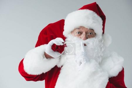 Photo for Santa claus holding bag and gesturing for silence isolated on white - Royalty Free Image