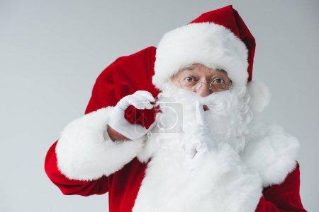Foto de Santa claus bolsa de sujeción y gesto de silencio aislado en blanco - Imagen libre de derechos