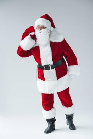 Photo for Full length view of santa holding bag full of presents and looking away - Royalty Free Image