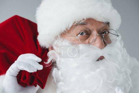 Photo for Close-up view of santa claus in eyeglasses holding bag and looking at camera - Royalty Free Image