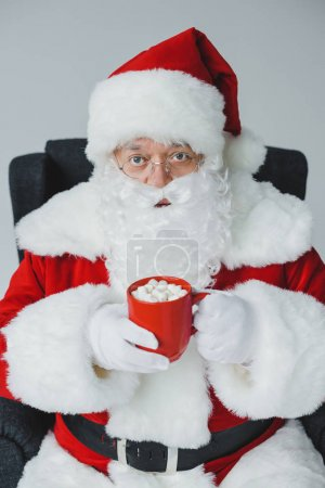 Photo for Santa claus drinking hot chocolate with marshmallows and looking at camera while sitting in chair - Royalty Free Image