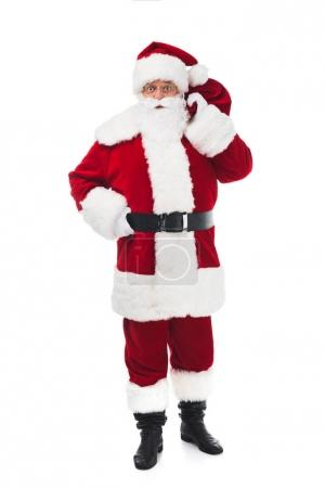Photo for Full length view of santa claus holding bag with presents and looking at camera isolated on white - Royalty Free Image