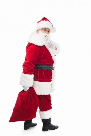 Photo for Santa claus holding bag with presents and gesturing for silence isolated on white - Royalty Free Image