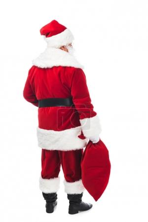 Photo for Back view of santa claus in traditional costume holding bag with presents isolated on white - Royalty Free Image