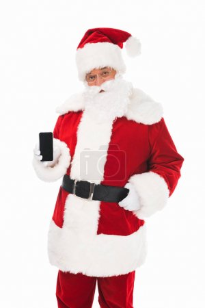 Photo for Santa claus holding smartphone with blank screen and looking at camera - Royalty Free Image