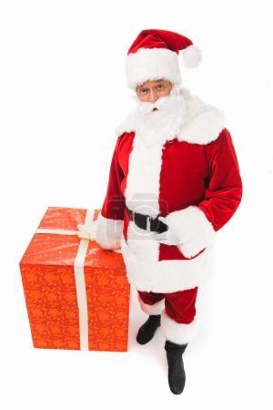 Photo pour Vue de la forte inclinaison du père Noël debout avec gros coffret rouge isolé sur blanc - image libre de droit