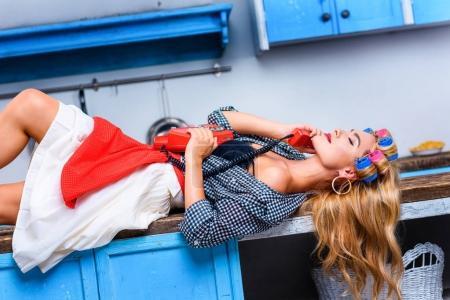 Foto de Seductora mujer en rulos hablando por teléfono vintage mientras se está acostado en la mesa - Imagen libre de derechos