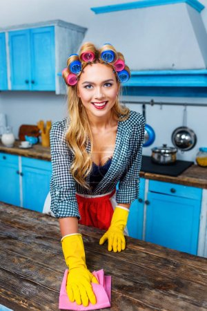 Photo for Beautiful smiling housewife with rag cleaning tabletop in kitchen - Royalty Free Image