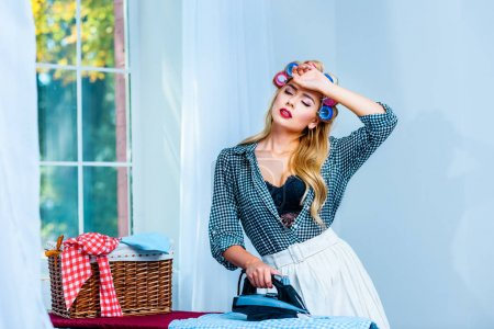 Photo for Attractive tired housewife in curlers ironing laundry - Royalty Free Image