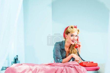 Photo pour Attrayant souriant femme au foyer parler au téléphone tout en repassant la lessive - image libre de droit