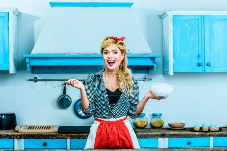 Photo for Beautiful excited pin up girl cooking in kitchen - Royalty Free Image