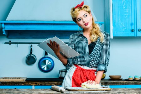 Photo for Thoughtful housewife reading cookbook while making dough in kitchen - Royalty Free Image