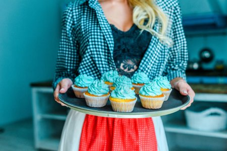 woman in apron with cupcakes