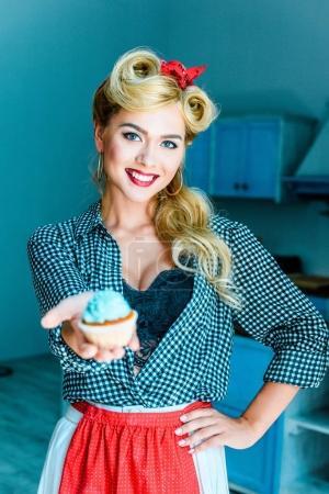 Photo pour Jolie femme dans la pin up style tenant cupcake dans cuisine - image libre de droit