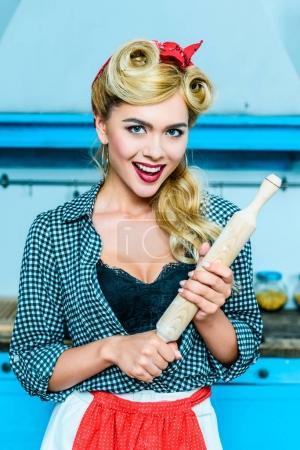 Photo pour Excité à attrayant pin-up ménagère tenant le rouleau à pâtisserie en cuisine - image libre de droit