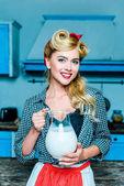 housewife holding milk jug