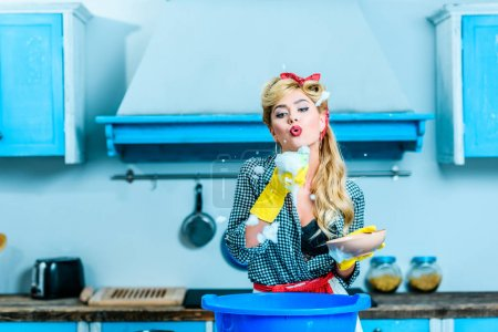 Photo for Beautiful blonde pin up girl blowing foam while washing dishes in kitchen - Royalty Free Image