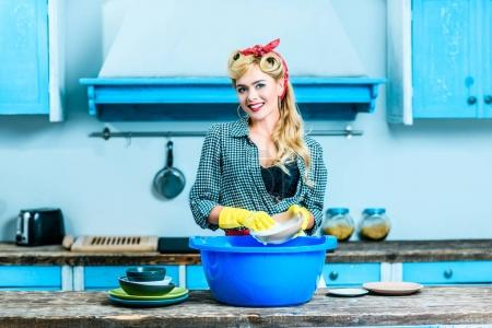Photo for Beautiful smiling housewife in pin up style washing dishes in kitchen - Royalty Free Image