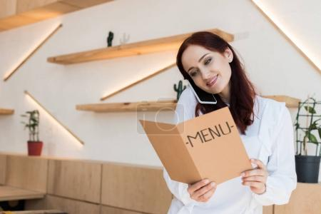 woman talking by phone and looking at menu