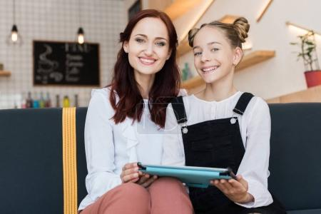 mother and daughter with tablet in cafe