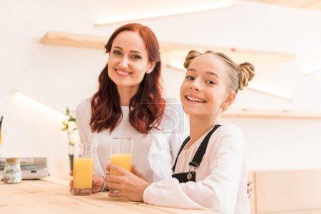 Foto de Madre e hija en café beber zumo de naranja - Imagen libre de derechos