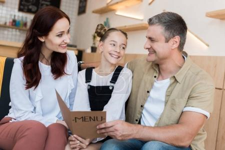 family looking at menu list in cafe