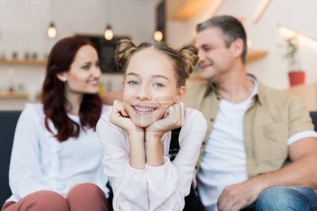 Photo for Teen girl looking at camera with her parents blurred on background - Royalty Free Image