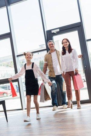 Photo pour Belle famille sur le shopping avec des sacs marchant par le centre commercial - image libre de droit
