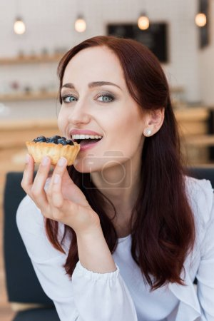 Photo for Young beautiful woman eating delicious dessert in cafe - Royalty Free Image