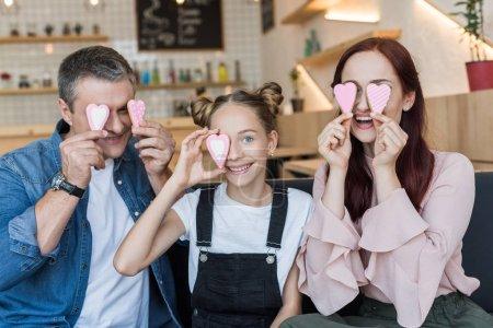 Photo pour Heureux famille couvrant les yeux avec des biscuits en forme de coeur dans le café - image libre de droit