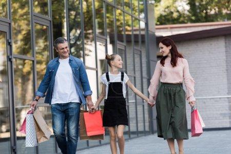 Photo pour Belle famille heureuse marche avec des sacs shooping - image libre de droit