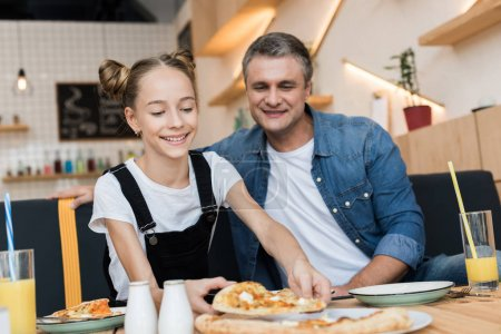 father and daughter eating pizza