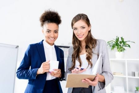 young businesswomen with coffee and notebook