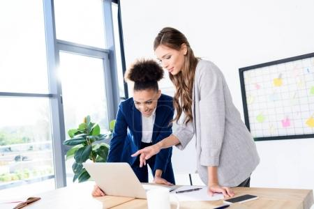 Photo for Young multiethnic businesswomen using laptop in office - Royalty Free Image