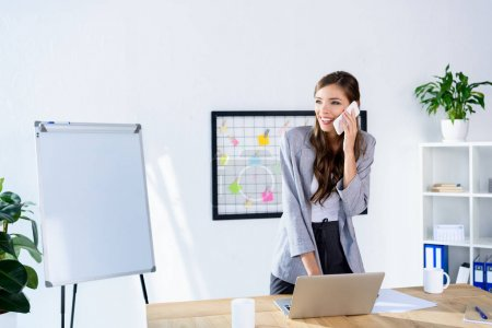 Photo for Smiling young businesswoman talking on smartphone and using laptop while working in office - Royalty Free Image
