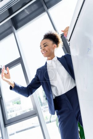 Photo for Smiling young african american businesswoman working with whiteboard - Royalty Free Image