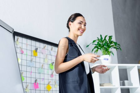 Photo for Attractive smiling asian businesswoman looking away in office - Royalty Free Image