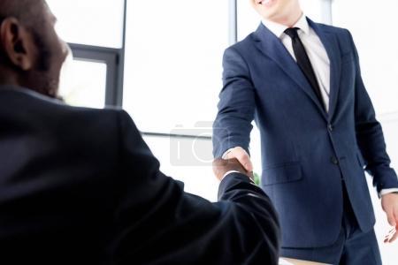 Photo pour Recadrée tir de jeunes entrepreneurs multiethniques se serrant la main au bureau - image libre de droit