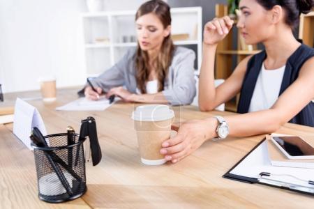 Photo pour Vue rapprochée de la tasse de café en papier et multiethnique businesswomen travaillant derrière - image libre de droit