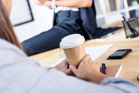 Photo pour Vue partielle de la femme d'affaires détenant le café pour aller sur les lieux de travail au bureau - image libre de droit