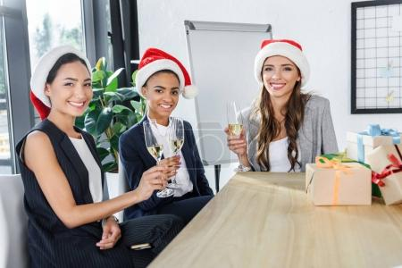 businesswomen drinking champagne in office