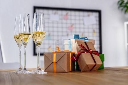 Photo pour Vue rapprochée des verres de champagne et de coffrets-cadeaux sur la table au bureau - image libre de droit